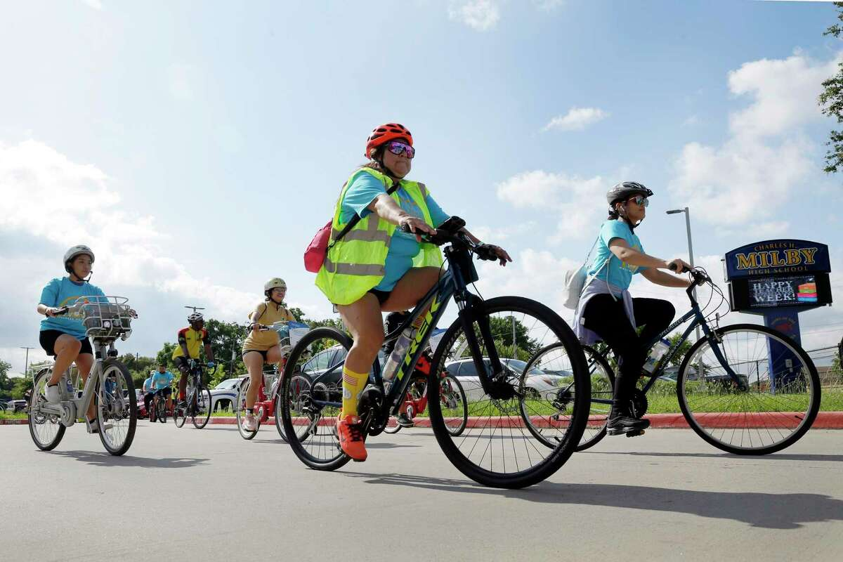 """Riders leave the parking lot as they begin this year's Communities in Schools """"Wellness On Wheels"""" bike ride, part of Mental Health Awareness Week, beginning at Mibly High School Saturday, May. 15, 2021 in Houston, TX. Over 40 riders participated in the ride, which included teens and city leaders."""
