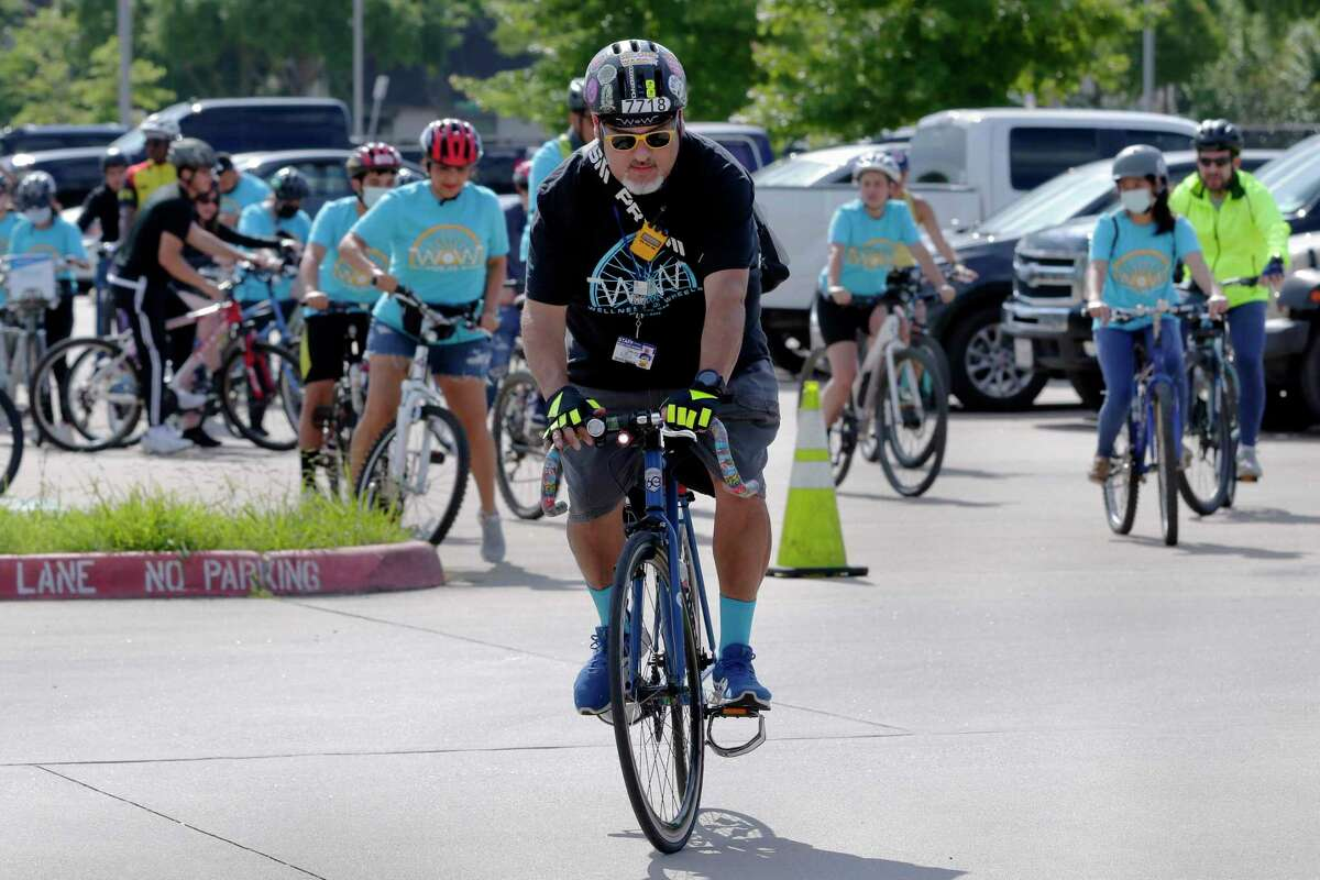 """Event organizer and ride leader Rene Gonzalez leads the procession of bikes as they leave the parking lot during this year's Communities in Schools """"Wellness On Wheels"""" bike ride, part of Mental Health Awareness Week, beginning at Mibly High School Saturday, May. 15, 2021 in Houston, TX. Over 40 riders participated in the ride, which included teens and city leaders."""