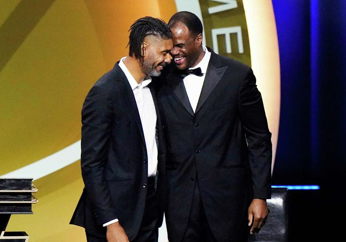 Tim Duncan, left, smiles with presenter David Robinson after being enshrined with the 2020 Basketball Hall of Fame class Saturday, May 15, 2021, in Uncasville, Conn.
