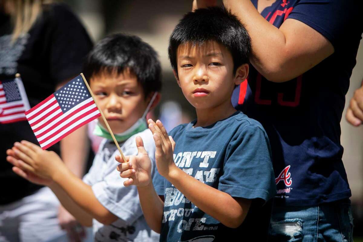 Brothers Lawrence, left, and Linus, center, clap during a