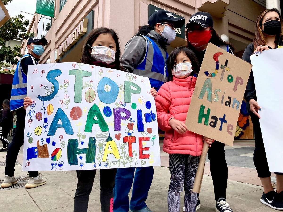 Naomi Ng and Vienna Ng, 7 year old twins, hold hand-drawn signs during a national Unity rally in Oakland, Calif. on Saturday, May 15, 2021.