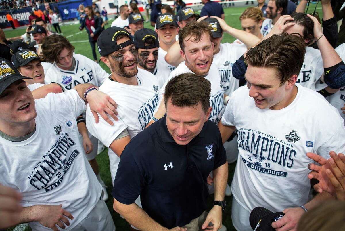 Yale players and coach Andy Shay celebrate after defeating Duke to win the NCAA men's championship on May 28, 2018.