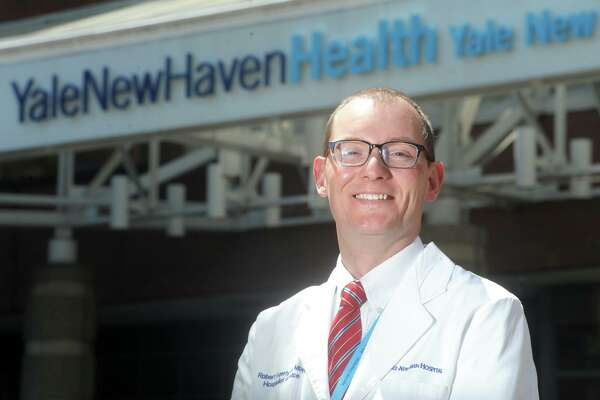 Dr. Rob Fogerty poses in front of Yale New Haven Hospital, in New Haven, Conn. May 14, 2021. Fogerty is director of bed resources at the hospital.
