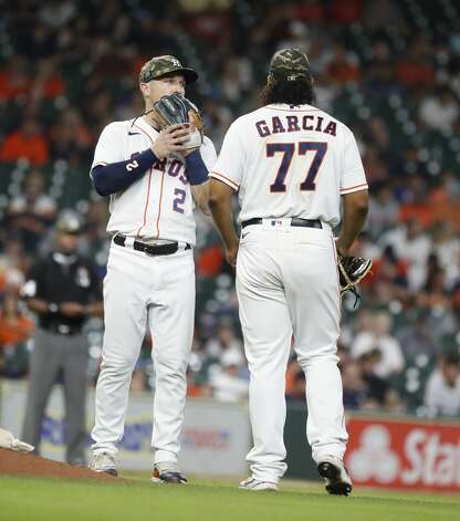 Houston Astros starting pitcher Luis Garcia (77) chats with Alex Bregman after walking Texas Rangers Nick Solak during the fifth inning of an MLB baseball game at Minute Maid Park, Saturday, May 15, 2021, in Houston. Photo: Karen Warren/Staff Photographer / @2021 Houston Chronicle