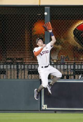 Houston Astros center fielder Myles Straw (3) jumps up to grab Texas Rangers David Dahl's fly out at the wall during the sixth inning of an MLB baseball game at Minute Maid Park, Saturday, May 15, 2021, in Houston. Photo: Karen Warren/Staff Photographer / @2021 Houston Chronicle