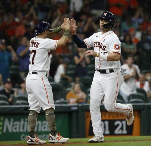 Houston Astros Aledmys Diaz (16) celebrates with Jose Altuve after they scored runs on Alex Bregman's RBI single off of Texas Rangers starting pitcher Dane Dunning during the first inning of an MLB baseball game at Minute Maid Park, Saturday, May 15, 2021, in Houston. Photo: Karen Warren/Staff Photographer / @2021 Houston Chronicle
