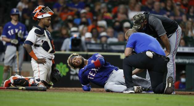 Texas Rangers Willie Calhoun (5) on the ground after he fouled a ball off his leg against Houston Astros relief pitcher Ryan Pressly during the ninth inning of an MLB baseball game at Minute Maid Park, Saturday, May 15, 2021, in Houston. Photo: Karen Warren/Staff Photographer / @2021 Houston Chronicle