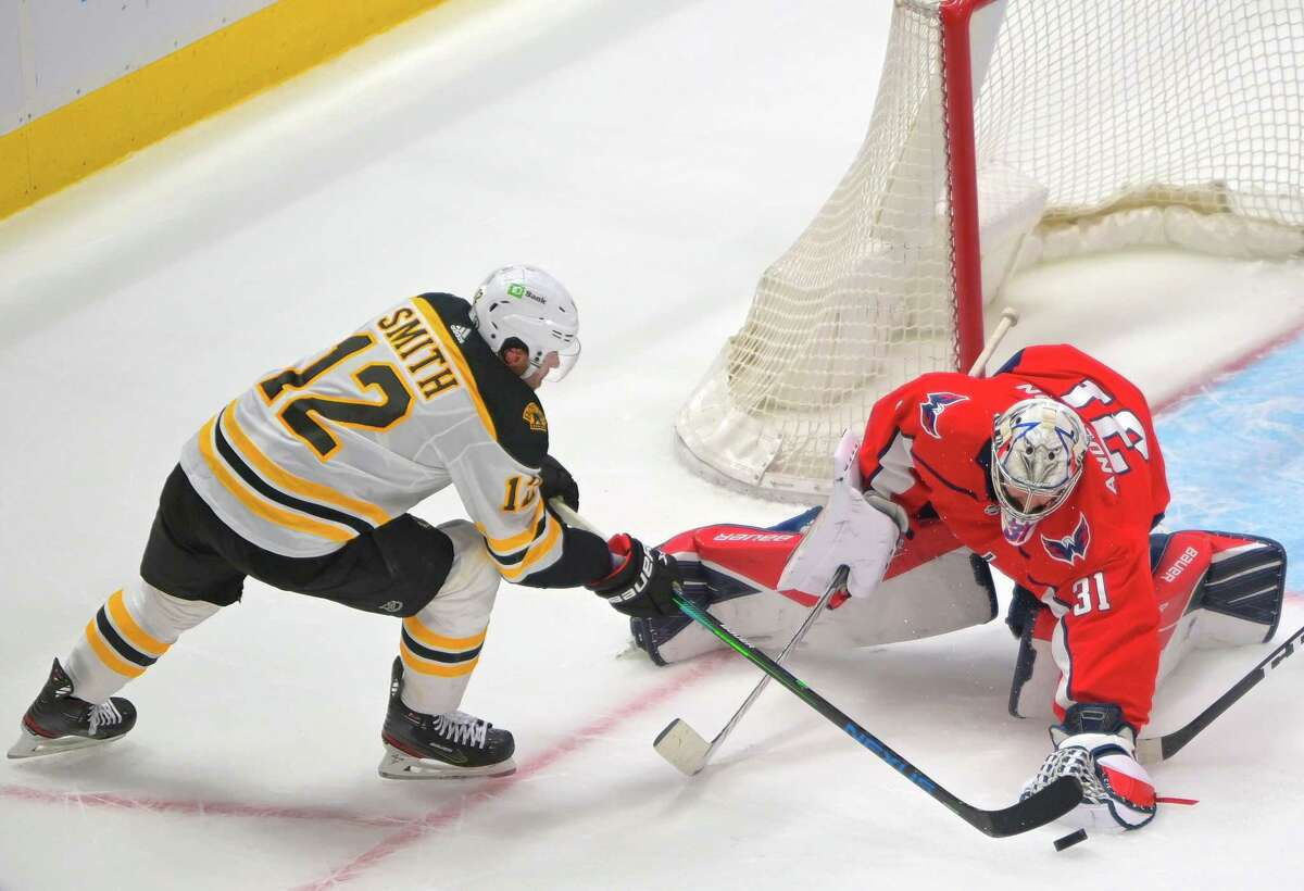 Bruins right wing Craig Smith, left, and Capitals goaltender Craig Anderson compete for the puck in the front of the net during Game 1 of their playoffs series Saturday night at Capital One Arena in Washington, D.C.