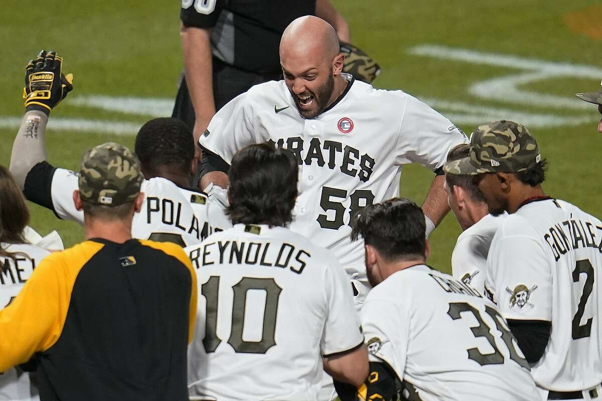 Pittsburgh Pirates' Jacob Stallings (58) is surrounded by teammates as he steps on home plate after hitting a two-run home run off San Francisco Giants relief pitcher Jake McGee during the ninth inning of a baseball game in Pittsburgh, Saturday, May 15, 2021. The Pirates won 8-6.(AP Photo/Gene J. Puskar)