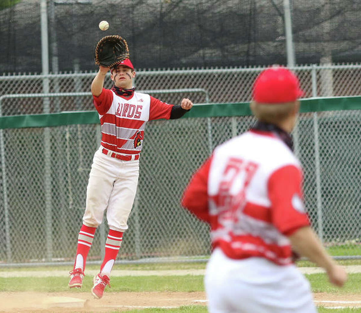 Alton first baseman Owen Macias (left) takes a throw from third baseman Jayden Diaz too late to prevent an infield hit for the Tigers in the fourth inning Saturday at Alton High in Godfrey.