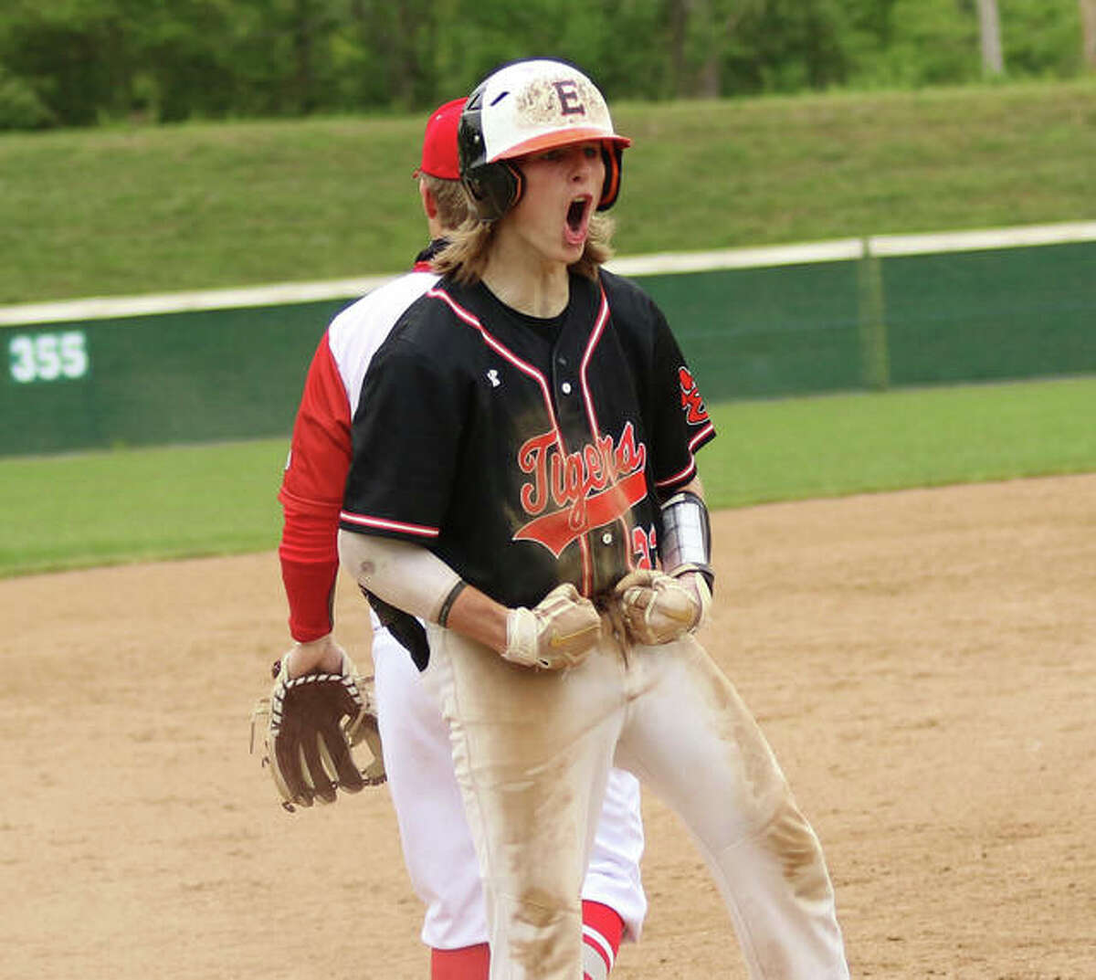 Edwardsville's Grant Huebner reacts with teammates in the dugout after his bases-loaded triple drove in three runs to start the scoring in the Tigers' 10-run fourth inning against Alton on Saturday morning in a SWC baseball game at Alton High in Godfrey.