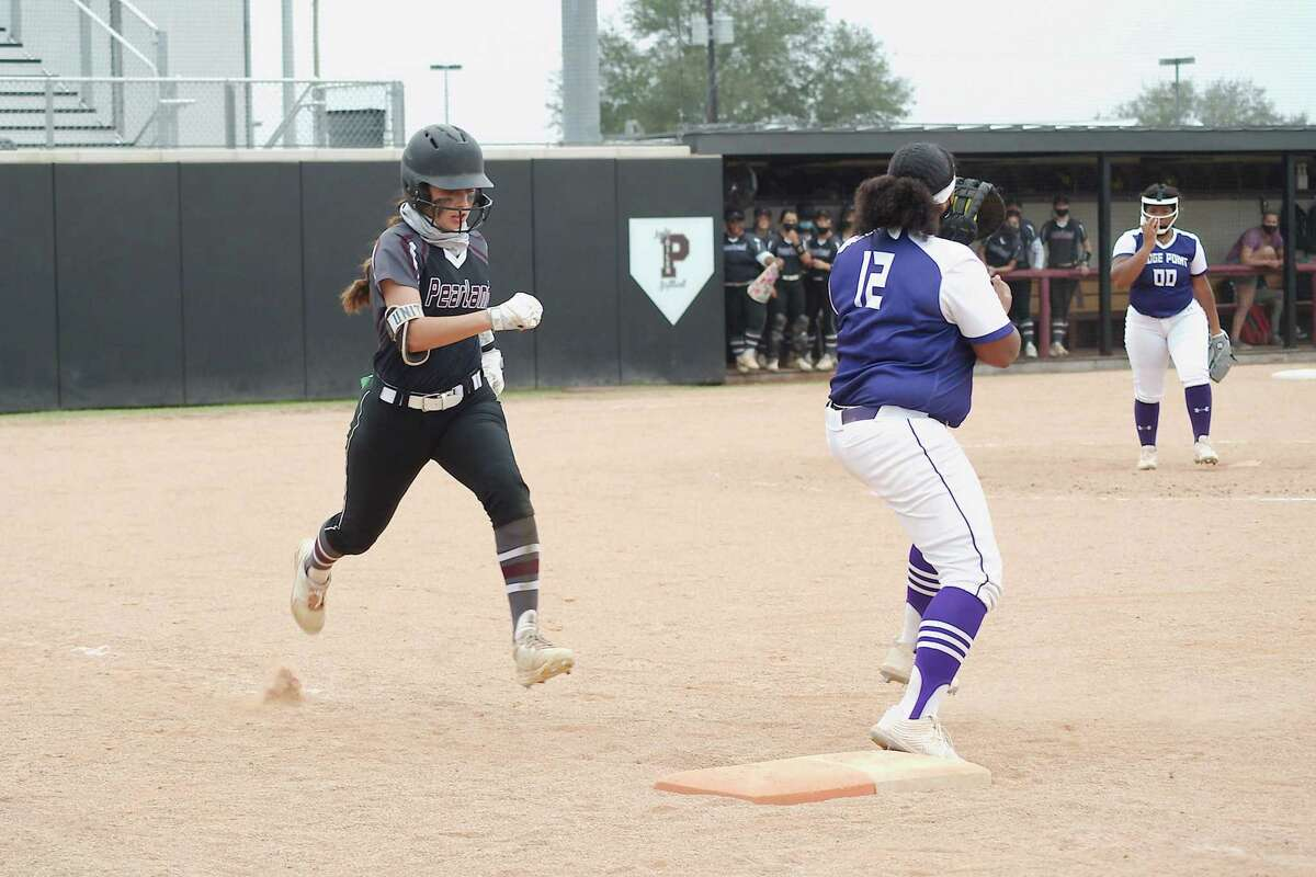 Pearland's Gabrielle Davila (21) tries to beat the throw to Ridge Point's Reagan Green (12) Saturday, Feb. 27 at Pearland High School.