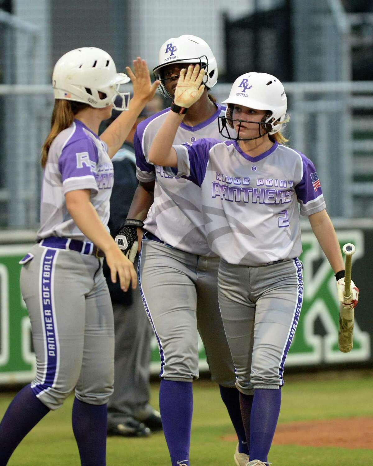 Payton Jackson (7), Taylor Roman (8), and Malyn Simmons (2) of Ridge Point celebrate after scoring on a hit by Maggie Darr (22) during the third inning of a Class 6A Region III playoff softball game between the Ridge Point Panthers and Cy Creek Cougars on Wednesday, May 1, 2019 at Mayde Creek High School, Katy, TX.