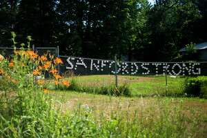 """""""Sanford Strong"""" is spelled out along a fence across the street from Penny Tyler, whose childhood home was demolished earlier Wednesday, July 8, 2020 in preparation for a new home to be built free of cost thanks to Great Lakes Homes in Freeland. (Katy Kildee/kkildee@mdn.net)"""