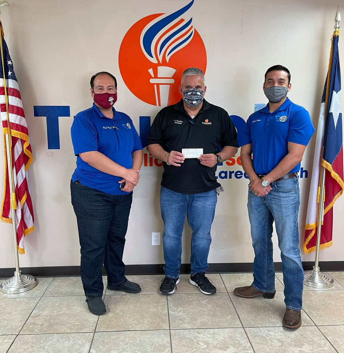 Webb County Treasurer Raul Reyes, left, and South Texas Latino Coalition President Jeronimo Martinez presented Triumph Public High School South Laredo Principal Odie Arambula a check for $300 to help purchase graduation caps and gowns for 10 graduating high school seniors.