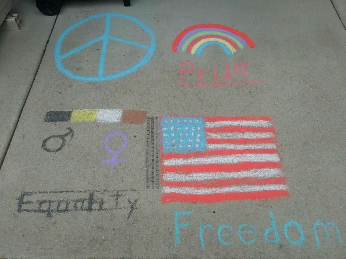 Residents of Manistee Place Apartments were invited to make chalk drawings outside of their apartments Sunday in an effort to enhance a feeling of community. (Kyle Kotecki/News Advocate)