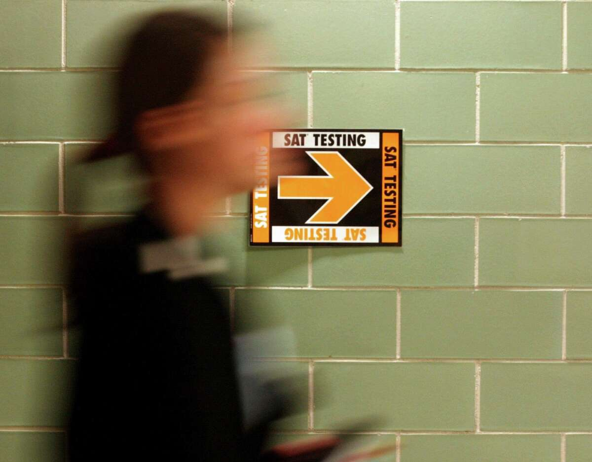 This file photo shows a student leaving after taking the SAT at Upper Arlington High School in Upper Arlington, Ohio.Reduced use of standardized tests in the college admissions process has led some college officials to question their value as indicators of college readiness and success.(AP Photo/Paul Vernon, File)