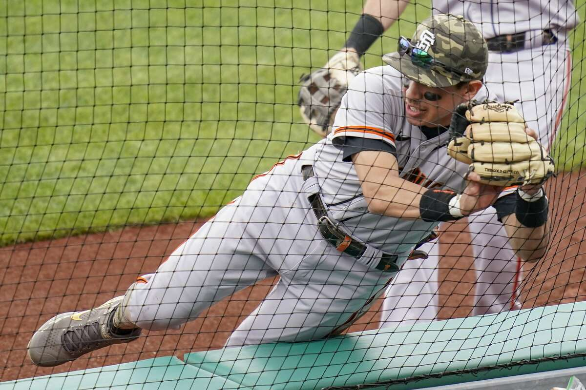 Giants second baseman Mauricio Dubón tumbles into the netting after catching Kevin Newman's foul ball in the fifth.