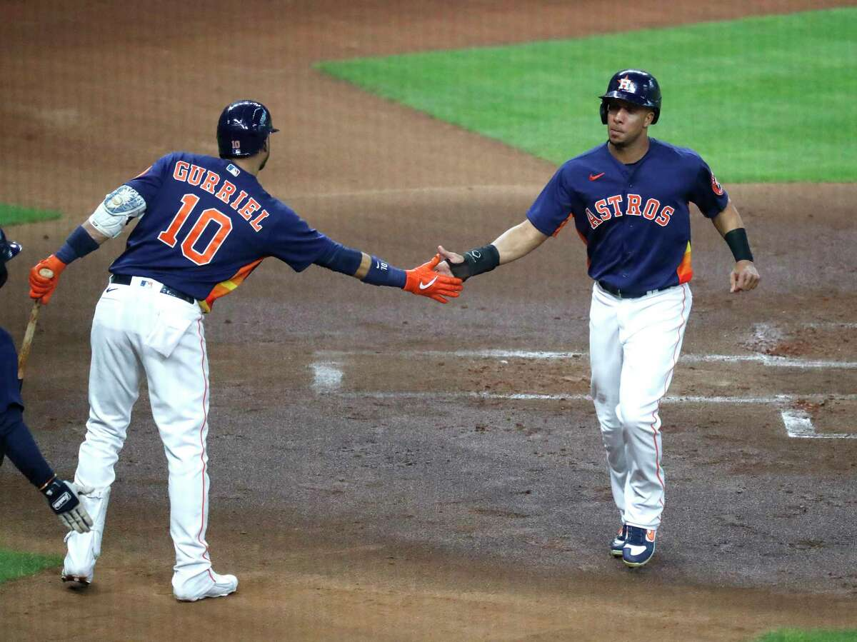 Houston Astros Michael Brantley (23) celebrates his run scored with Yuli Gurriel (10) on Alex Bregman's RBI single during the first inning of an MLB baseball game at Minute Maid Park, Sunday, May 16, 2021, in Houston.