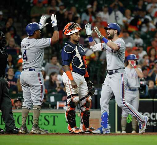Texas Rangers David Dahl (21) celebrates his two-run home run off of Houston Astros relief pitcher Andre Scrubb with Khris Davis (4) during the seventh inning of an MLB baseball game at Minute Maid Park, Sunday, May 16, 2021, in Houston. Photo: Karen Warren, Staff Photographer / @2021 Houston Chronicle