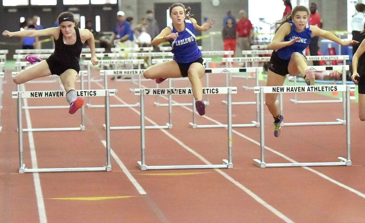 New Haven, Connecticut - Saturday, February 10, 2018: 50-meter hurdles champion Elizabeth Herlihy of Shelton H.S, left, beats second-place finisher Tess Stapleton of Fairfield-Ludlowe H.S., center, and third place finisher Nora Skoczen of Fairfield-Ludlowe H.S., right, during the 2018 State Class LL Girls and Boys Indoor Track and Field Championship at the Floyd Little Athletic Center in New Haven.
