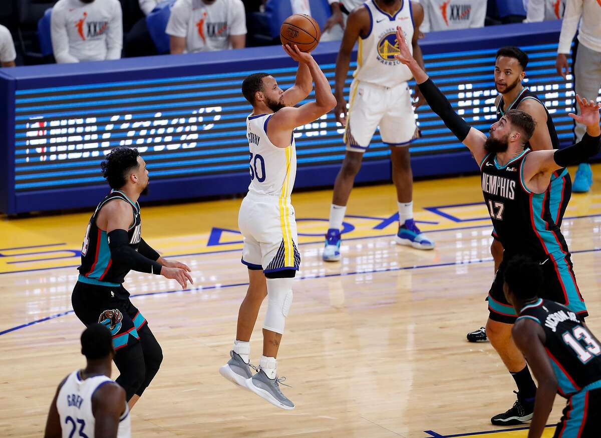Golden State Warriors' Stephen Curry shoots between Memphis Grizzlies' Jonas Valanciunas and Dillon Brooks in first quarter during a game at Chase Center in San Francisco, Calif., on Sunday, May 16, 2021.