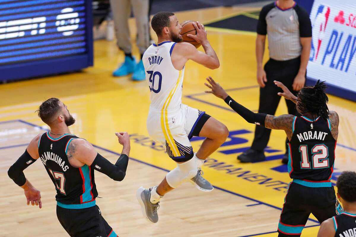 Warriors guard Stephen Curry scores between the Grizzlies' Jonas Valanciunas and Ja Morant during the first quarter of the season finale at Chase Centern Francisco, Calif., on Sunday, May 16, 2021.
