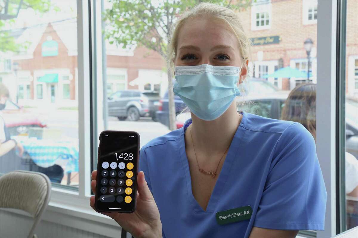 Kimberly Hibben, a registered nurse whose parents own Grieb's Pharmacy in Darien, proudly shows her calculation of the 1,428 COVID shots she herself has administered to date.