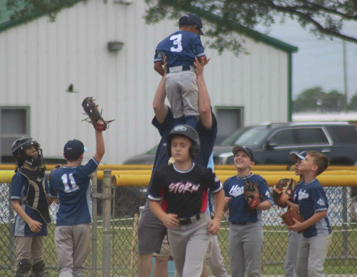 Hooks player and winning pitcher Daniel Sanchez gets held high in the air by a member of the coaching staff after the team rallied from a 5-0 deficit Saturday.