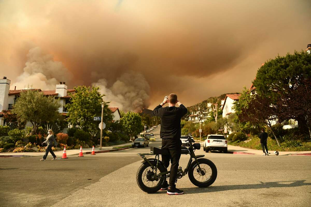 A man photographs smoke from the Palisades Fire in Topanga State Park, near Los Angeles.
