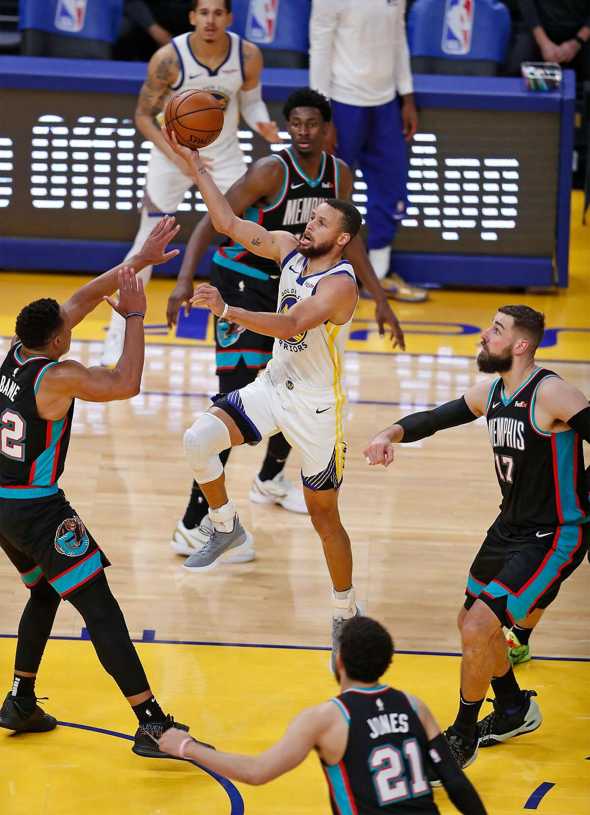 Golden State Warriors' Stephen Curry scores between four Memphis Grizzlies in 4th quarter of Warriors' 113-101 win during NBA game at Chase Center in San Francisco, Calif., on Sunday, May 16, 2021.