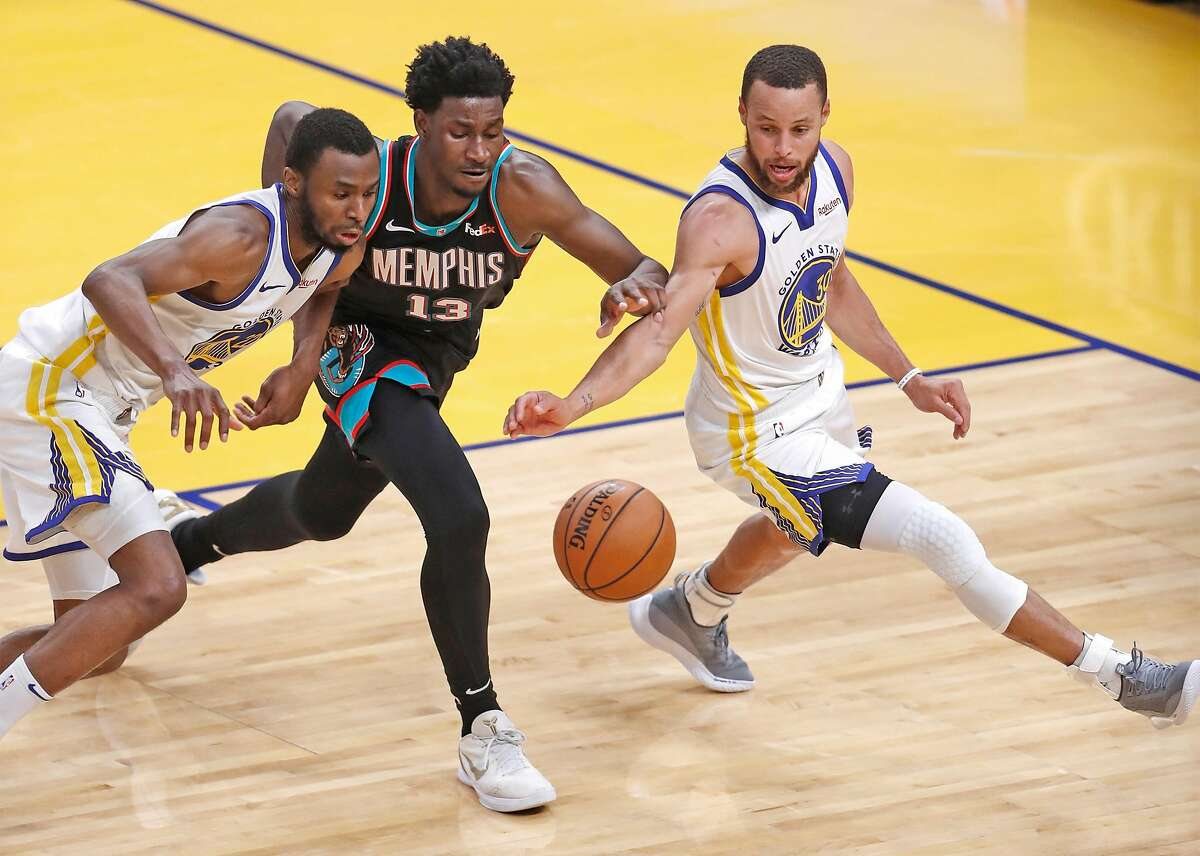 Golden State Warriors' Andrew Wiggins and Stephen Curry vie for a loose ball against Memphis Grizzlies' Jaren Jackson Jr. in 4th quarter during Warriors' 113-101 win in NBA game at Chase Center in San Francisco, Calif., on Sunday, May 16, 2021.