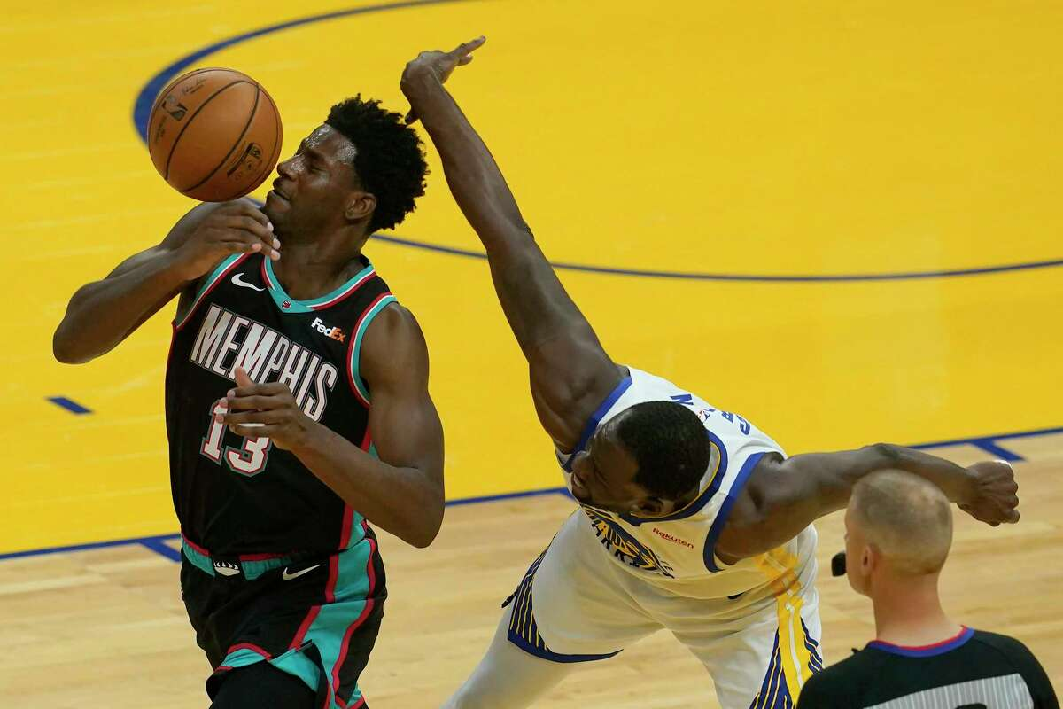 Memphis Grizzlies forward Jaren Jackson Jr. (13) looks for the ball in front of Golden State Warriors forward Draymond Green during the first half of an NBA basketball game in San Francisco, Sunday, May 16, 2021.