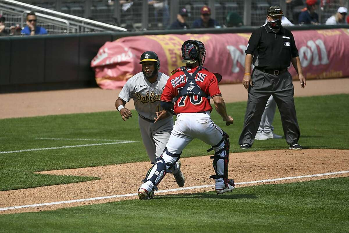 Minnesota Twins catcher Ben Rotvedt, right, makes contact with the A's Elvis Andrus and is called for interference allowing Andrus to score during the fifth inning of Sunday's game.