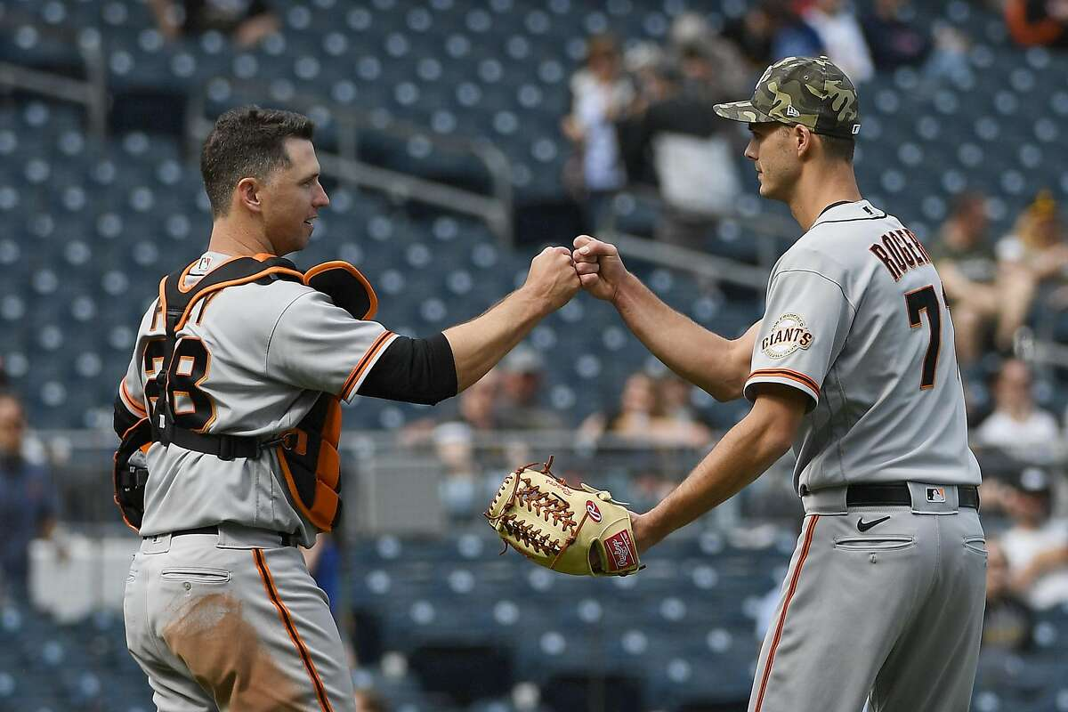 Giants' reliever Tyler Rogers and catcher Buster Posey bump fists after the final out in Sunday's 4-1 defeat of the Pittsburgh Pirates.
