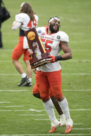Sam Houston State defensive lineman Jahari Kay (55) runs off the field with the championship trophy as he celebrates SHSU's 23-21 win over South Dakota State to capture the NCAA FCS national football championship on Sunday, May 16, 2021, in Frisco. Photo: Brett Coomer/Staff Photographer / © 2021 Houston Chronicle