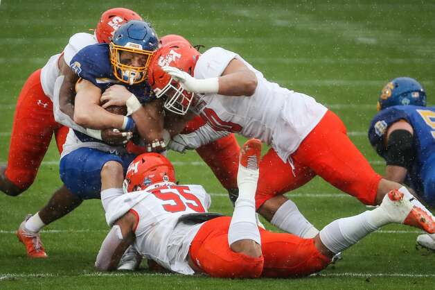 Sam Houston State defensive linemen Jahari Kay (55) and Trace Mascorro (90) stop South Dakota State running back Isaiah Davis (22) during the first quarter of the NCAA FCS national football championship game on Sunday, May 16, 2021, in Frisco. Photo: Brett Coomer/Staff Photographer / © 2021 Houston Chronicle