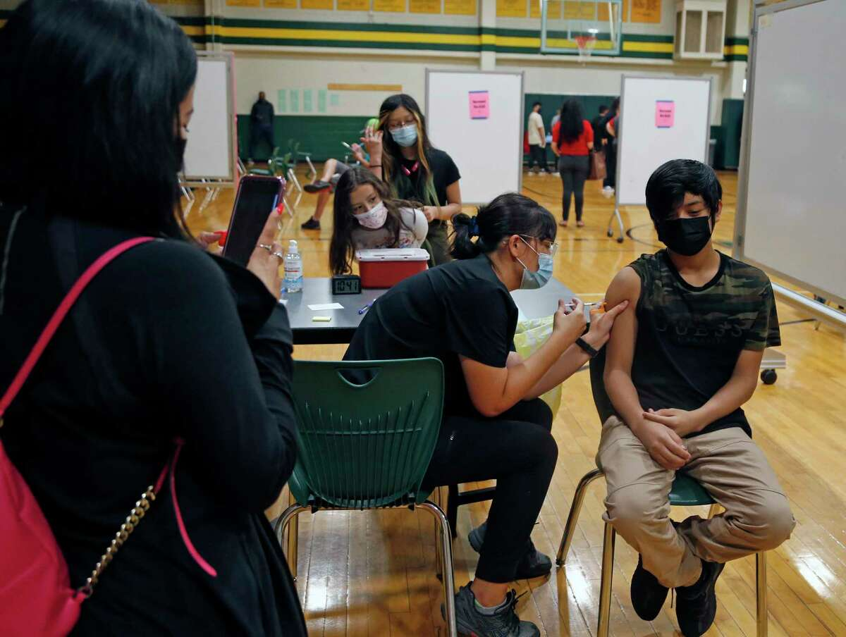 Sonia Schinder, a student at the University of the Incarnate Word, administers a COVID-19 vaccine to Edwin Segovia, 13, at a pop-up clinic at Sul Ross Middle School.