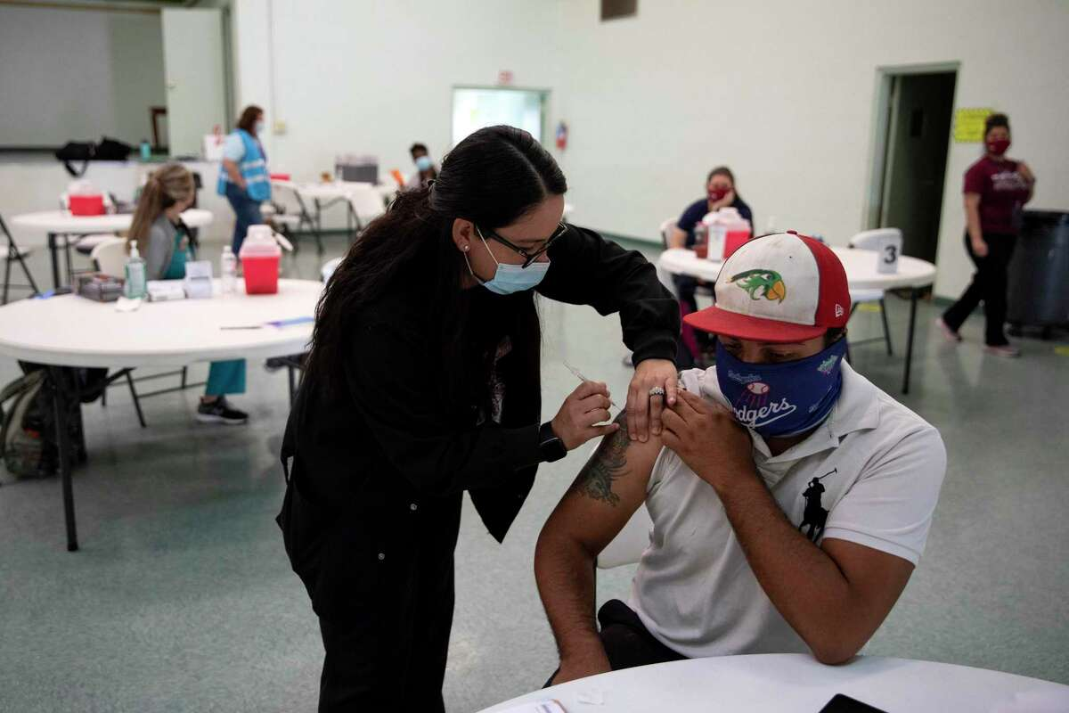 Luis Marquez receives his vaccine from Janet Porter, a nurse practitioner, at a mobile clinic organized by the city. Metro Health will be offering pop-up clinics at several Fiesta events.