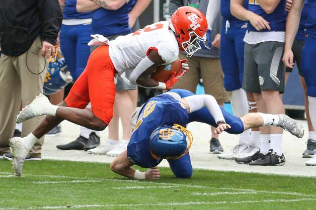 Sam Houston State wide receiver Ife Adeyi (2) dives over South Dakota State safety Chase Norblade (35) as he makes a reception for a first down during the second half of the NCAA FCS national football championship game on Sunday, May 16, 2021, in Frisco. Sam Houston took the title with a 23-21 win. Photo: Brett Coomer/Staff Photographer / © 2021 Houston Chronicle
