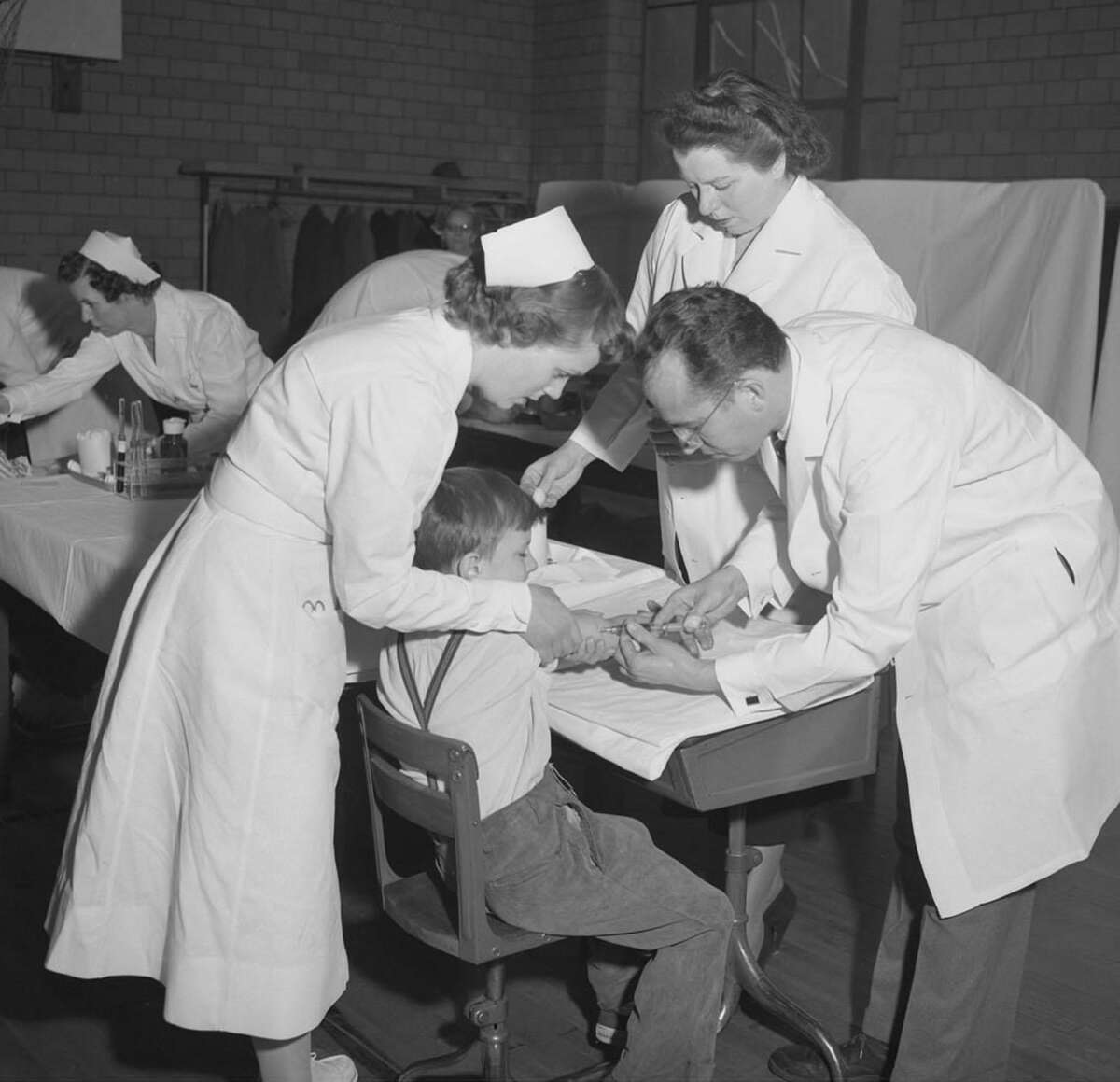 Dr. Jonas Salk, right, the Pittsburgh scientist who developed the polio vaccine, administers an injection to a boy at Arsenal Elementary School in Pittsburgh, Pennsylvania, Feb. 23, 1954.