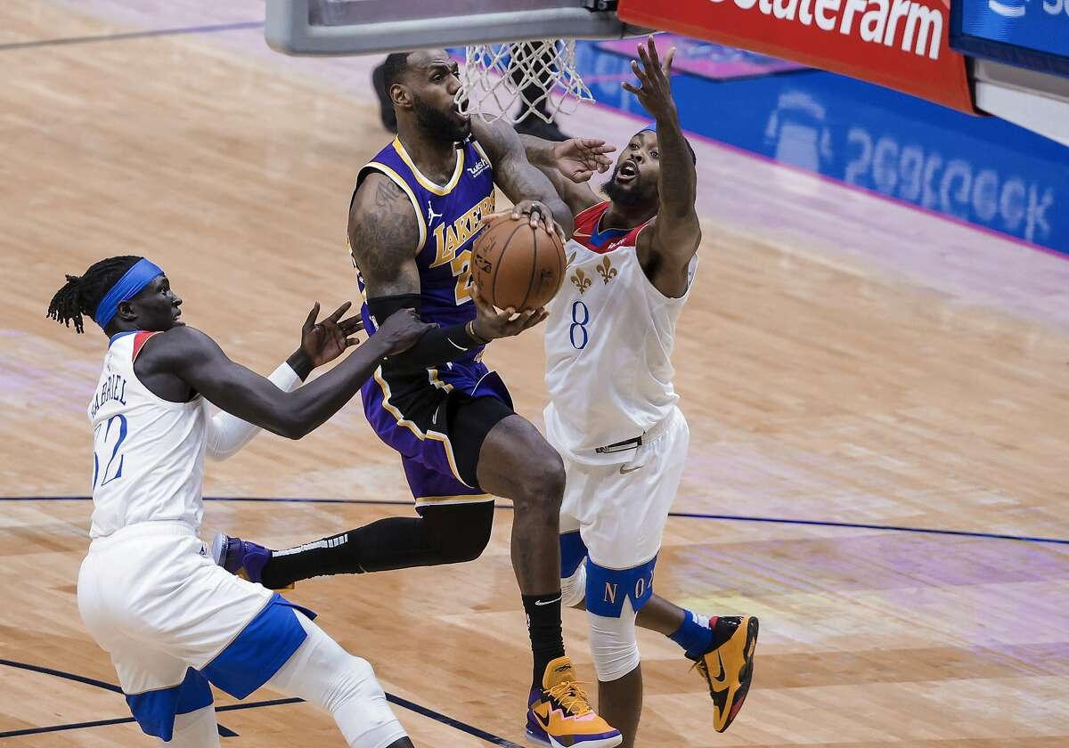 Los Angeles Lakers forward LeBron James (23) drives to the basket against New Orleans Pelicans forward Wenyen Gabriel (32) and forward Naji Marshall (8) in the second quarter of an NBA basketball game in New Orleans, Sunday, May 16, 2021. (AP Photo/Derick Hingle)