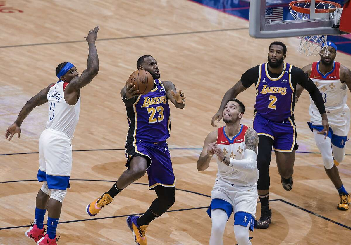 Los Angeles Lakers forward LeBron James (23) shoots as New Orleans Pelicans guard Eric Bledsoe (5) and center Willy Hernangomez (9) defend in the first quarter of an NBA basketball game in New Orleans, Sunday, May 16, 2021. (AP Photo/Derick Hingle)