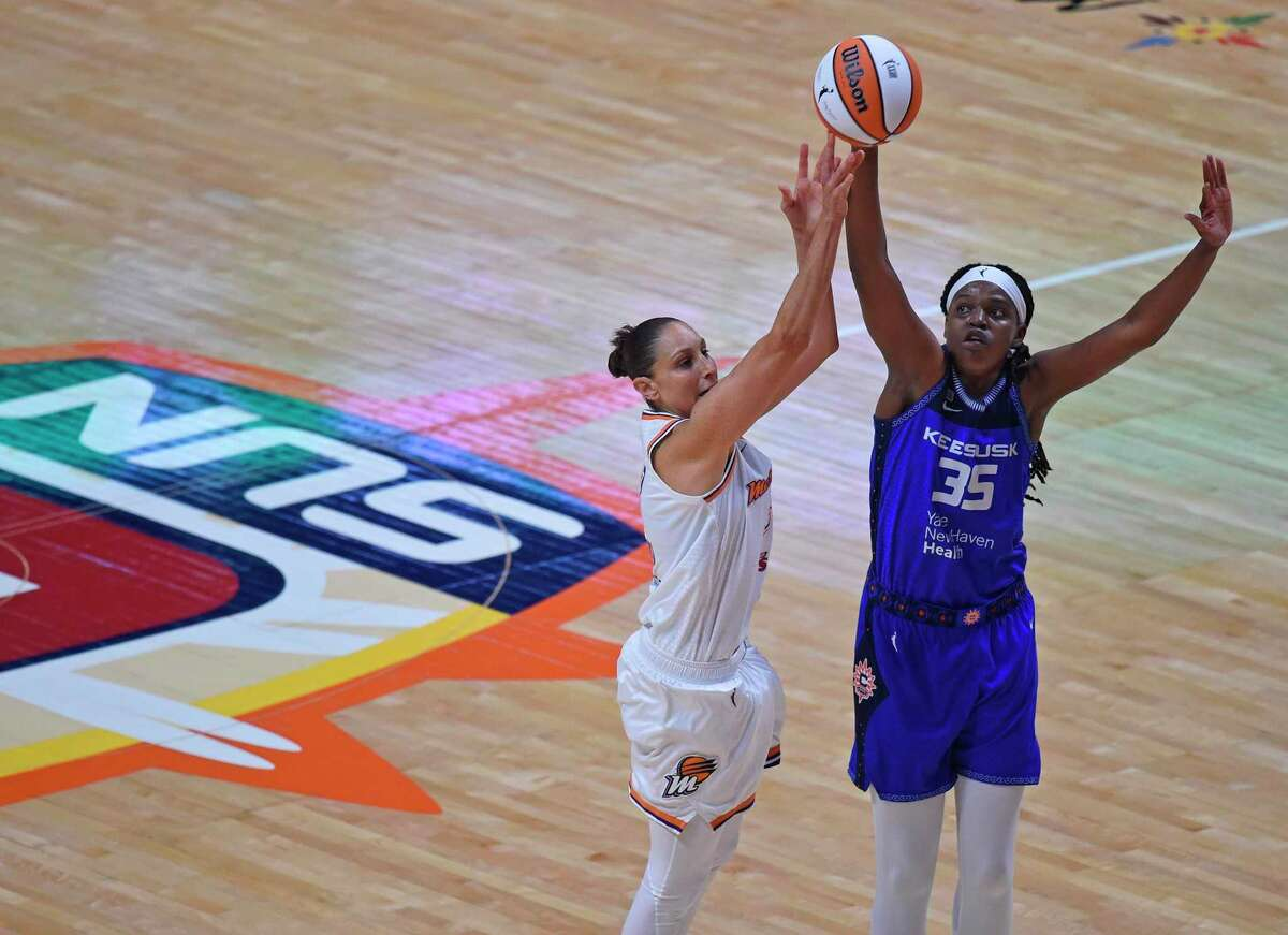Former UConn standout Phoenix Mercury guard Diana Taurasi, left, gets a shot off over Connecticut Sun forward Jonquel Jones, right, in the home opener Sunday, May 16, 2021, in Uncasville, Conn.