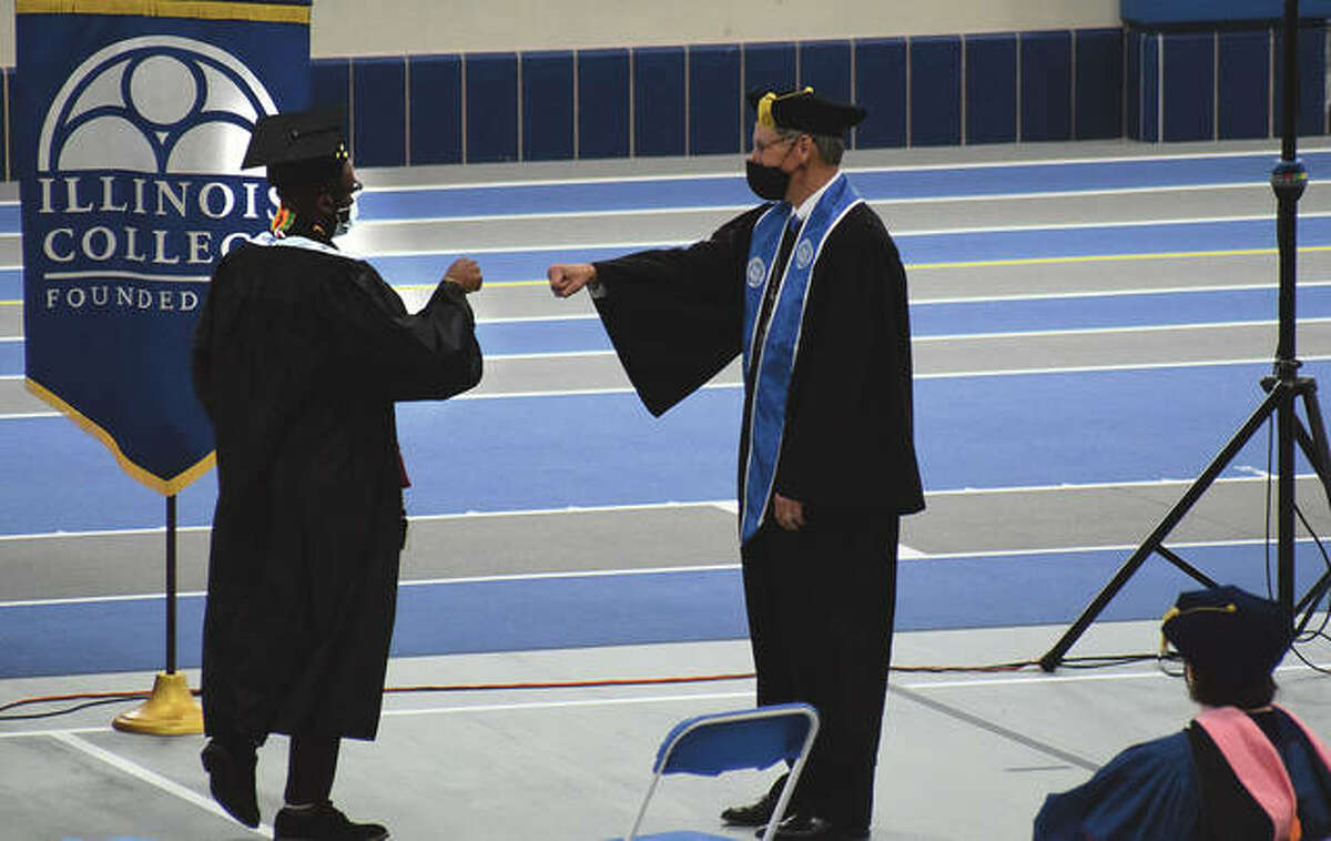 A graduating Illinois College student gets a congratulatory fist-bump before the start of the college's commencement ceremony.