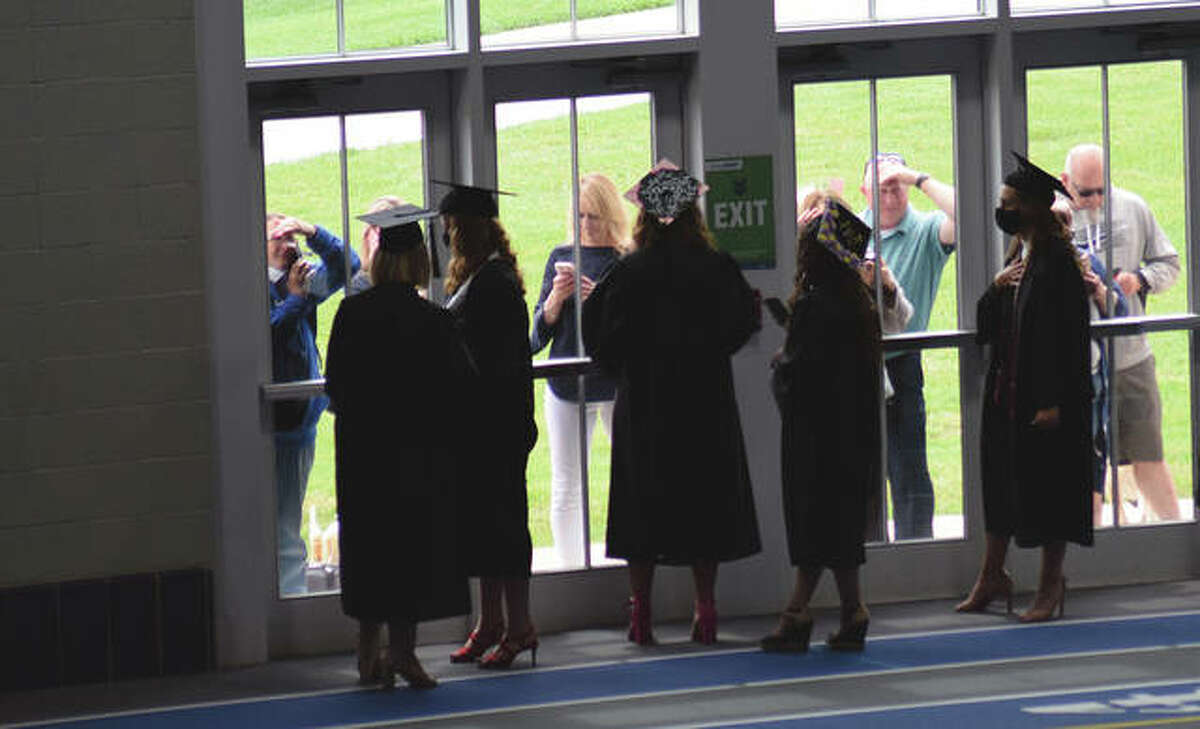 Graduating students greet some of those who gathered outside to watch Illinois College's commencement ceremony. In-person participation was limited because of pandemic protocol.