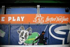 In this Tuesday, April 16, 2019 photo, a Hartford Yard Goats employee pulls a cart through the picnic pavilion area in the outfield of Dunkin' Donuts Park before a game between the Yard Goats and Richmond Flying Squirrels in Hartford, Conn. (AP Photo/Jessica Hill)