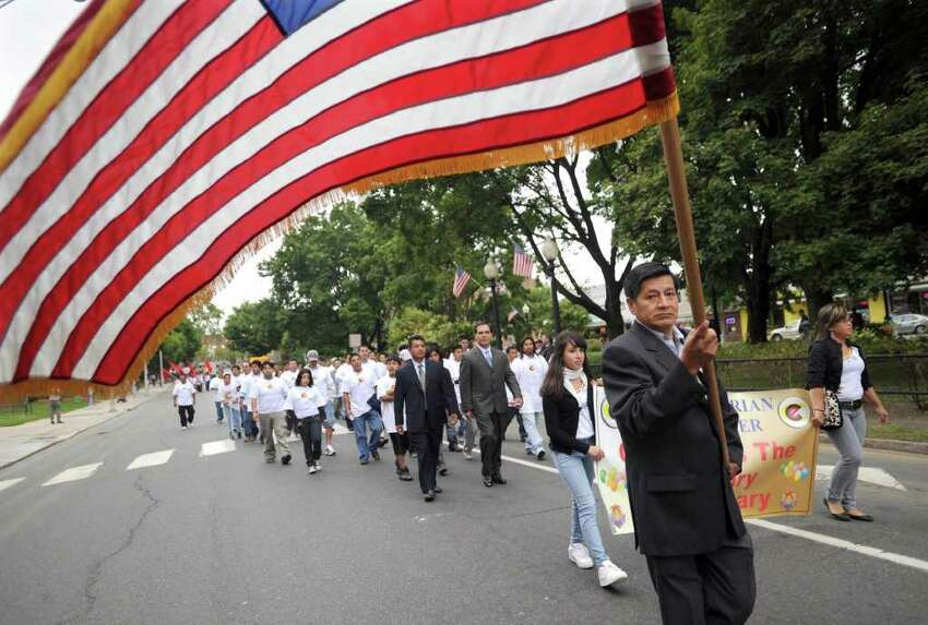 Angelo Tuva of Danbury carries an American flag while marching with the Danbury Ecuadorian Civic Center in the News-Times Community Parade Sunday, Sept. 12, 2010.