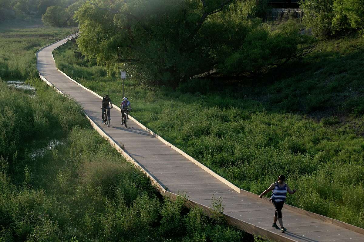 Cyclists and a pedestrian share the Salado Creek Greenway in September. Regreening San Antonio will help mitigate climate change here.
