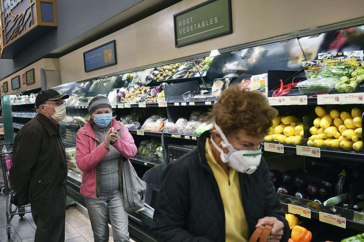 Customers wearing masks shop at a supermarket in Los Angeles on March 20, 2020.